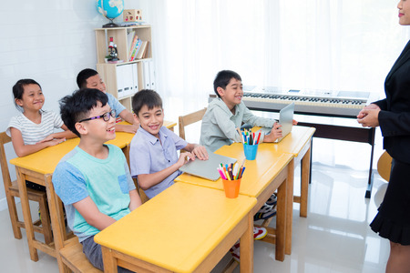Asian elementary school children smiling happily while teacher teaching in classroom