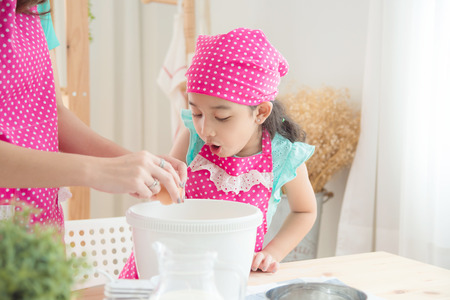 Mother and daughter wearing pink apron making cake in the kitchen. Stock Photo