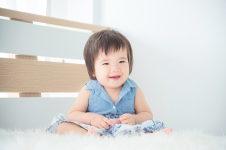 Little asian cute girl sitting and smiles on bed in bedroom