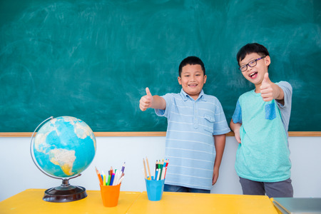 Two young asian student standing and smiling in front of chalkboard at school Stock Photo
