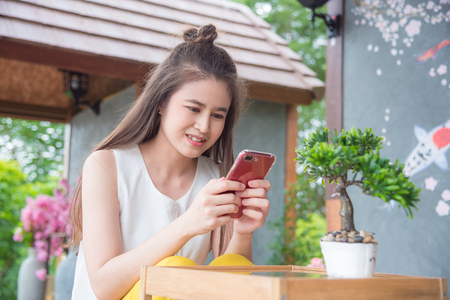 Beautiful asian girl using smartphone and smiles at home