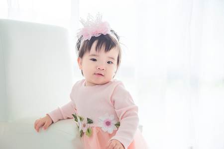 Little asian cute girl standing in front of bright window
