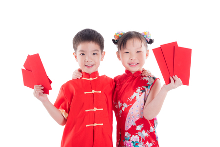 Two chinese children in traditional costume holding red packet money and smile over white background
