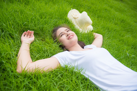 Beautiful asian gril lying on freash green grass field and smiles