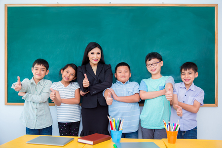 Group of happy asian student and teacher standing in classroom Stock Photo