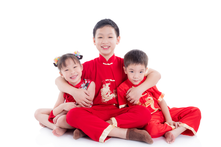 Group of chinese children wearing traditional costume sitting and smile on the floor over white background