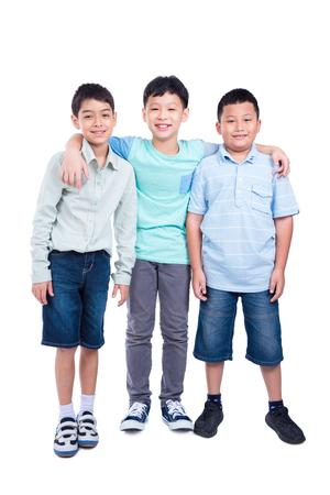 Full length of three school boy standing over white background