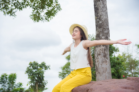 Beautiful Asian woman doing outstretched hands and smile with good nature in forest on the top hill