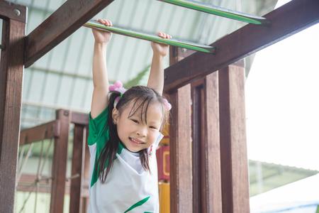 Little asian girl hanging bar in school playground