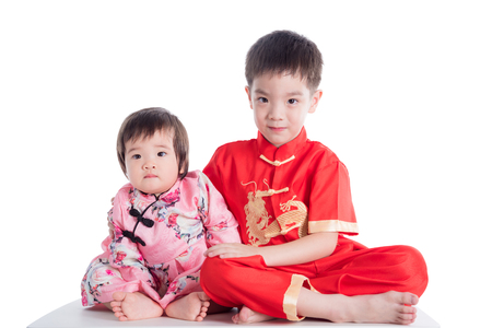 Two chinese children wearing traditional costume sitting on table over white background Stock Photo