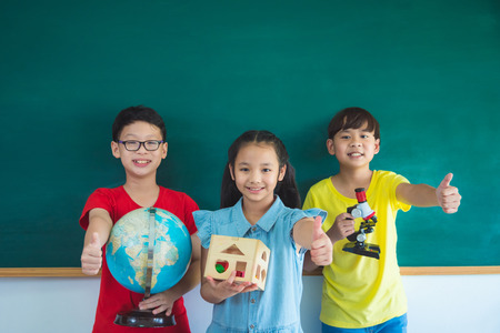 Three asian student smiling in front of chalkboard and showing thumb up