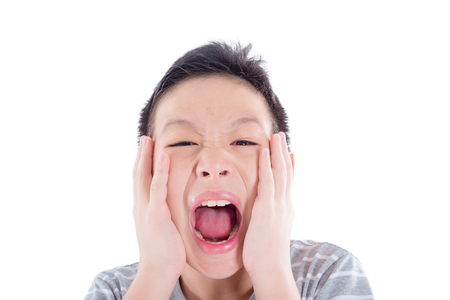 Asian teenager with acne on his face screaming isolated over white background