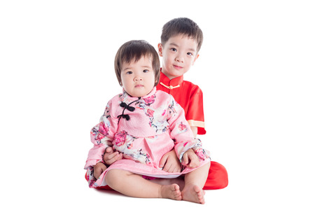 Two chinese children wearing traditional costume sitting and smile on the floor over white background