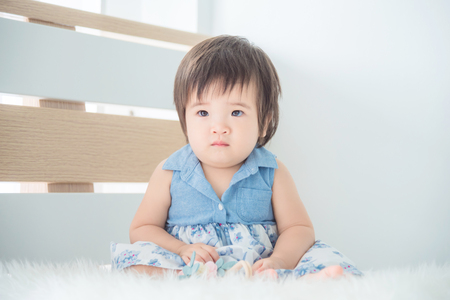 Little asian cute girl sitting on bed in bedroom Stock Photo