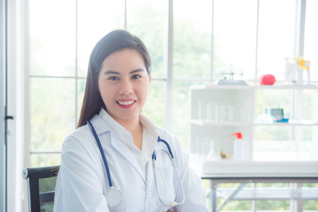 Beautiful asian doctor sitting in office and smiling at camera Stock Photo