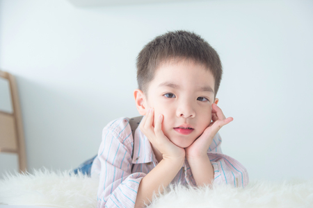 Young asian cute boy lying on bed and looking at camera