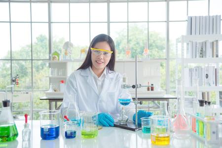 Lächelnder asiatischer Chemiker mit Schutzbrille und Mantel im Labor sitzend