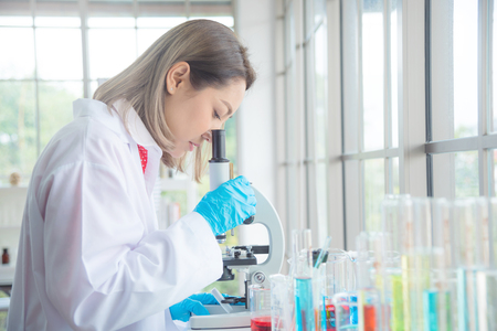 Beautiful asian scientist looking through a microscope in laboratory. Stock Photo