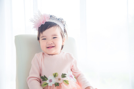 Little asian cute girl sitting and smiles on the chair