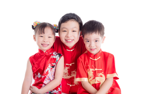 Group of chinese children wearing traditional costume smile at camera over white background Stock Photo