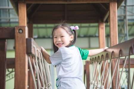 Little asian girl playing and smiles in school playground Stock Photo