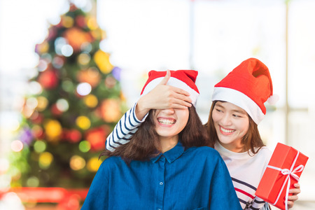 Asian woman couple,girlfriend close eyes by hand to surprise friend by giving Christmas gift in party.Holiday celebrating season,lesbian couple concept. Stock Photo