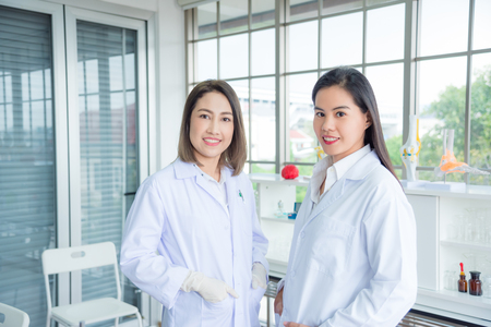 Beautiful asian medical student standing with young female medical professional teacher in classroom
