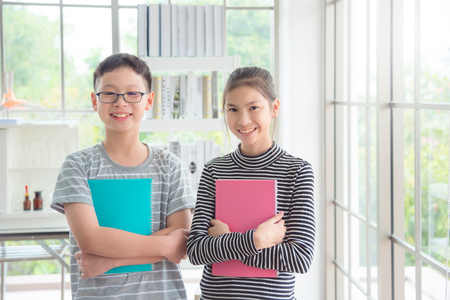 Young asian boy and girl standing and smiling in classroom