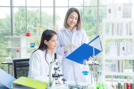 Two of asian female scientists in white coat working at the laboratory