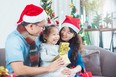 Asian family opening their presents together on Christmas morning. They are sitting on sofa in their living room in front of Christmas tree.
