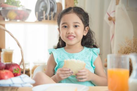Kleines asiatisches Mädchen, das Brot am Frühstückstisch isst