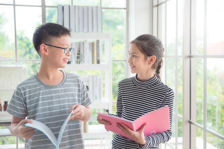 Jeune garçon et fille asiatique parlant et souriant en classe Banque d'images