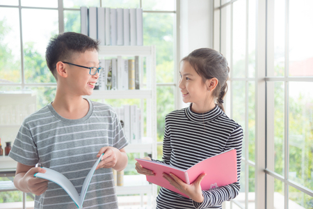 Young asian boy and girl talking and smiling in classroom Foto de archivo - 116215362