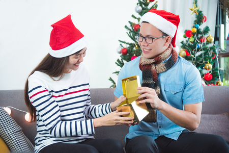 Asian boyfriend surprise girlfriend by giving Christmas present at sofa with xmas decoration tree at home,Holiday celebrating concept.