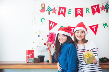 Two beautiful asian girls holding gift boxes and smile in Christmas party at home.