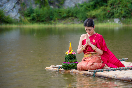 Beautiful Thai girl wearing red Thai traditional dress praying on river raft in Loy Krathong festival