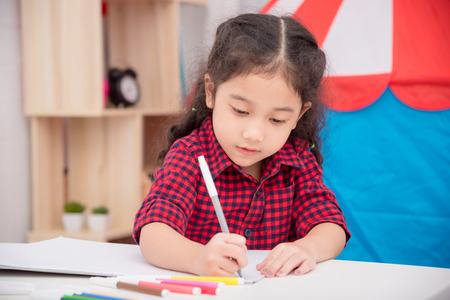 Little asian girl drawing picture by color marker on table at home