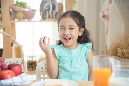 Little asian girl eating strawberry at breakfast table