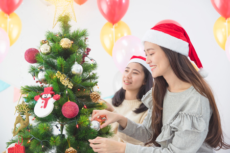 Beautiful asian girl with friend wearing Santa hats decorating Christmas tree at home for holidays. Stock Photo