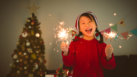 Little asian girl holding sparkle firework and smile in room with Christmas decoration at Christmas night