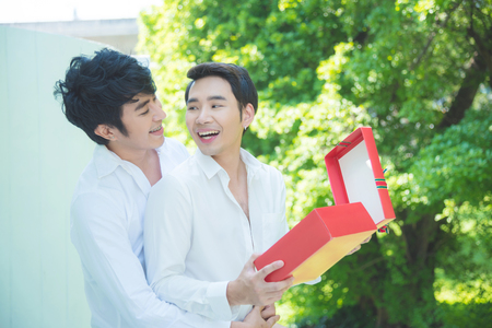 Young asian homosexual couple opening christmas gift box with smile together Stock Photo