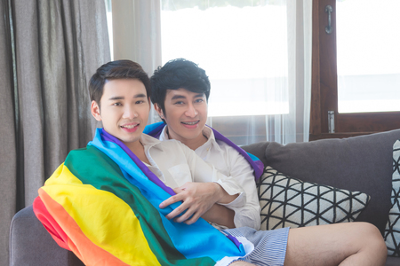 Young asian homosexual couple sitting together on sofa at home
