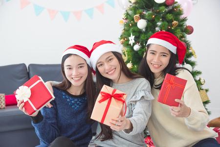 Three asian beautiful girl with santa hat holding gift box and smile at camera