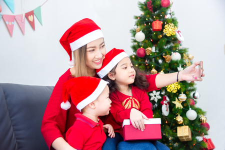Beautiful asian mother with her children wearing christmas costume and taking photo themself by smartphone at home with christmas decoration Stock Photo
