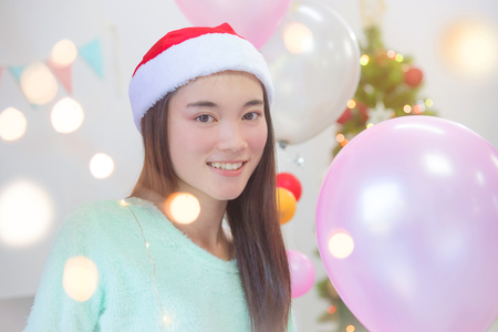 Beautiful asian girl with santa hat smiling in Christmas party Stock Photo