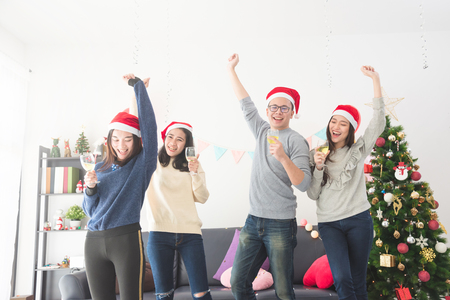 Three beautiful asian girls and a man celebrating Christmas or the New Years Eve with wine Stock Photo