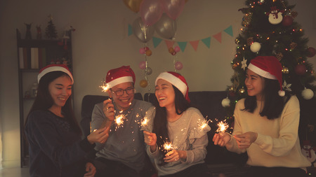 Group of asian young people celebrating Christmas party by sparkle firework