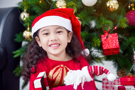 Little asian girl wearing santa hat and smiles while opening christmas gift at home