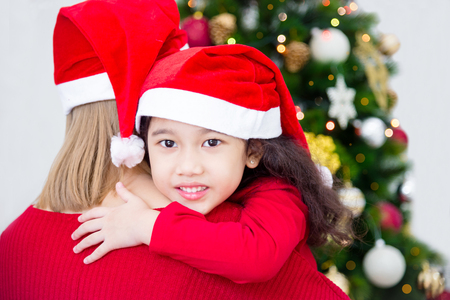 Mother and her daughter wearing christmas costume and smiling in room with Christmas tree decoration