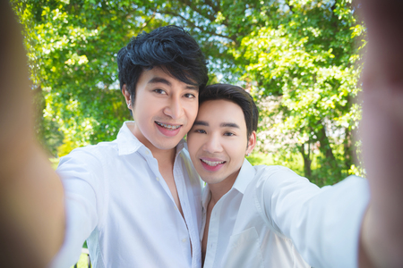 Young asian homosexual couple taking photo themself by smartphone